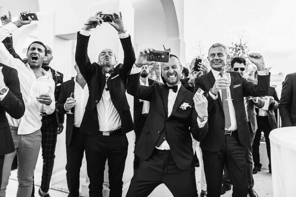 Photo noir et blanc d'hommes qui prennent des photos en s'amusant lors d'un mariage par Sébastien Roignant