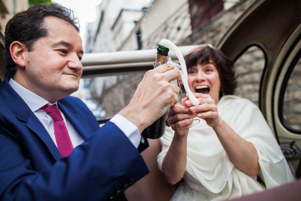 Photo spontanée de l'ouverture d'une bouteille de champagne dans une voiture entre 2 mariés par Sébastien Roignant