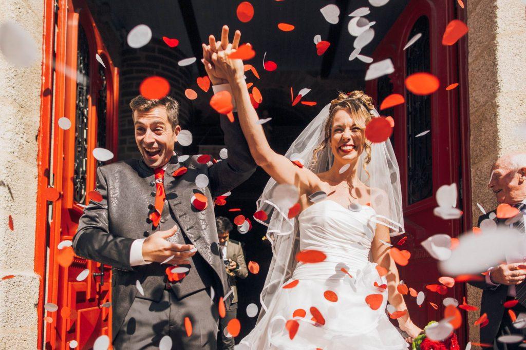 Photo colorée de jeunes mariés heureux qui sortent de la Mairie sous des confettis par Sébastien Roignant