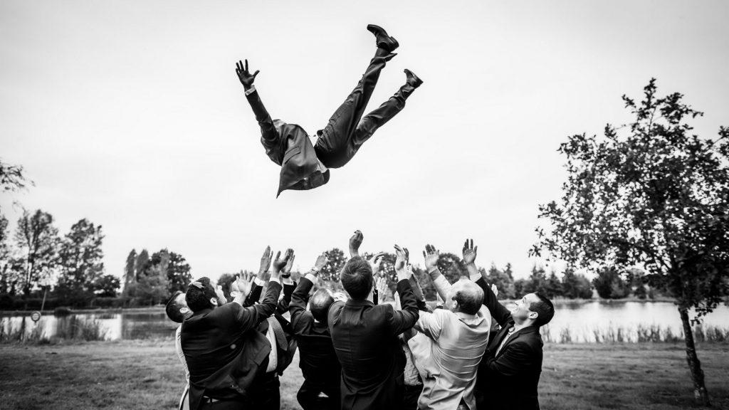 Photo en noir et blanc de Sébastient Roignant d'un marié propulsé en l'air par ses invités