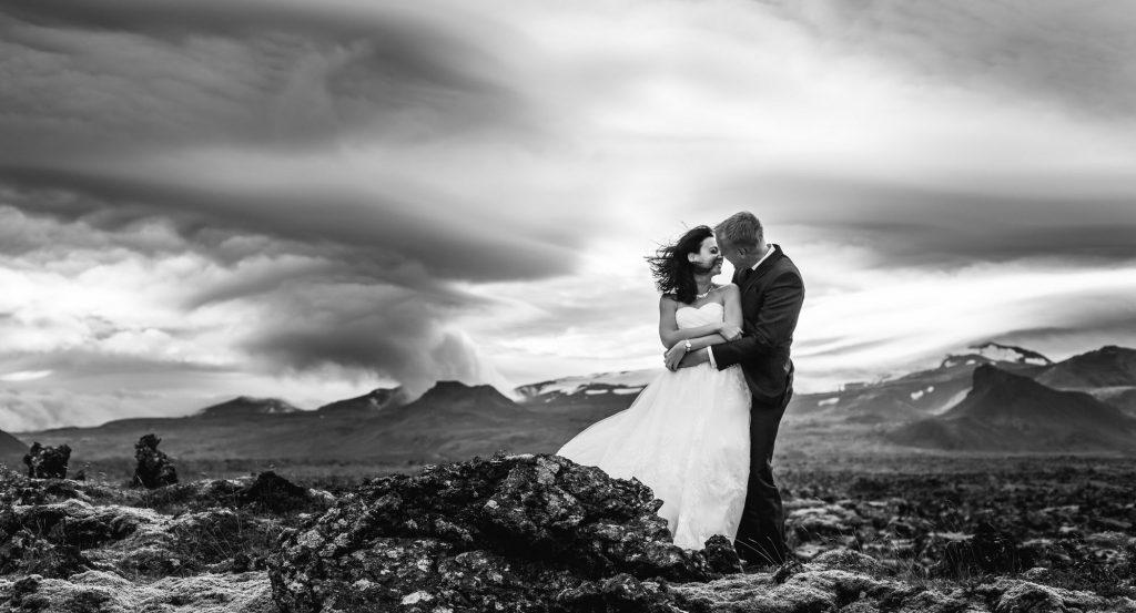 Photo en noir et blanc d'un moment de complicité entre 2 mariés devant un magnifique paysage nuageux par Sébastien Roignant