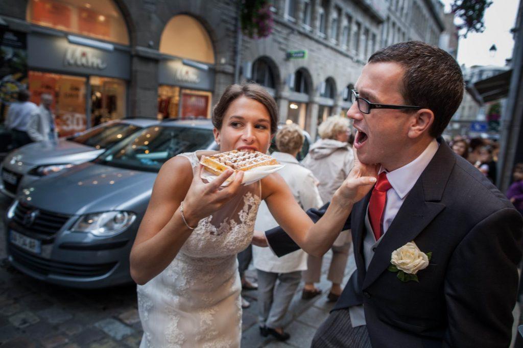 Photo amusante d'un moment complice d'un couple en tenue de mariage qui mange une gaufre dans la rue par Sébastien Roignant