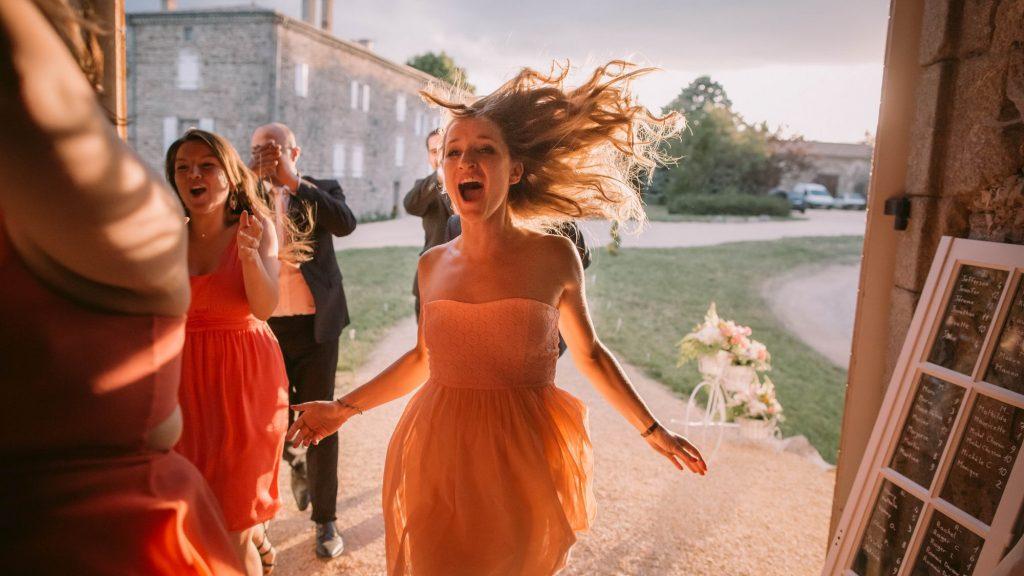 Photo colorée d'une jeune femme qui court à l'entrée d'un repas de mariage par Sébastien Roignant